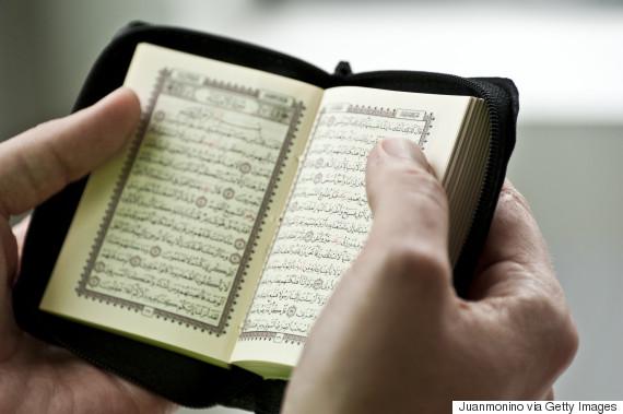 Man hands holding an open Holy Koran. Shallow depth of field.